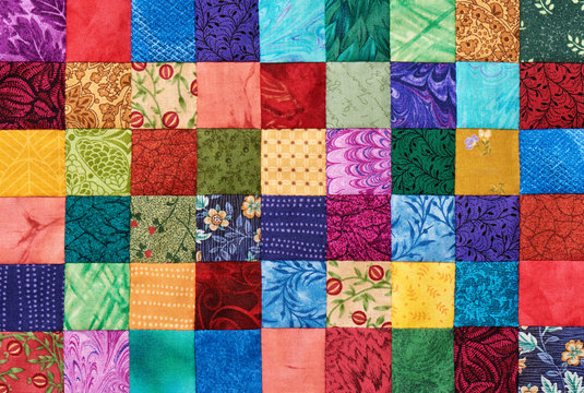 Colorful detail of quilt sewn from square pieces