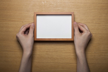 woman hand hold a photo frame on the wood table(background)