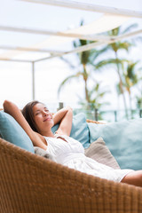 Luxury hotel lifestyle woman relaxing sleeping enjoying luxury sofa on outdoor patio living room. Happy lady lying down on comfortable pillows taking a nap for wellness and health.
