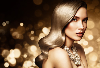 Fashion portrait of young caucasian model with gold jewelry on golden background. Beautiful blonde woman with long shiny hair. Glamour trendy accessories and hairstyle.