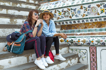 Girlfriends sitting down and rest after long trip in Wat po, Thailand