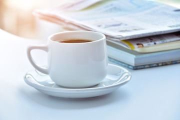 white coffee cup in morning with newspaper and book on table.