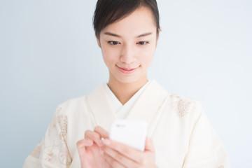 スマートフォンを使う着物姿の女性