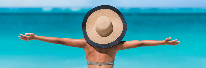 Wall Mural - Beach vacation freedom summer travel holidays banner panorama. Woman in sun hat and bikini with open arms raised to the sky enjoying looking view of beach blue ocean.