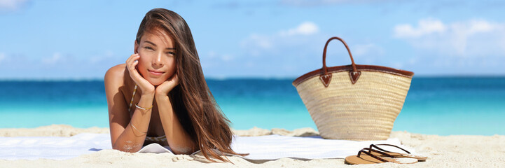 Wall Mural - Woman relaxing on beach vacation summer holidays banner with sky and blue ocean. Beautiful Asian girl lying down on towel with flips flops and beach bag tanning. Sun hair and skin care concept.