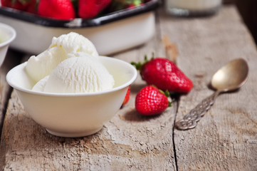 Vanilla ice-cream in a white small bowl with fresh ripe strawberries on a wooden background. Rustic style and close up. Summer food concept.