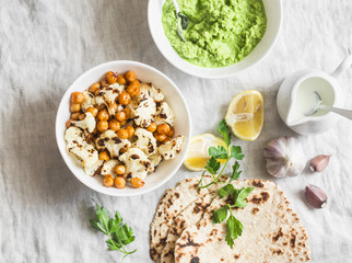 Gluten free flatbread, roasted chickpeas, cauliflower and avocado dip on a light background, top view. Healthy vegetarian food concept. Flat lay