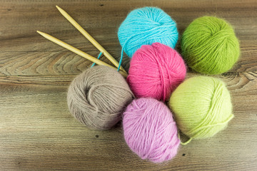 Colored wool balls with needles on a rustic wooden table