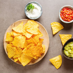 Snack for a party, chips with a tortilla, nachos with sauces: salsa with tomatoes, sour cream and guacamole. Mexican food. Dark background. Top view. Copy space