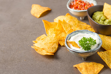 Snack for a party, chips with a tortilla, nachos with sauces: salsa with tomatoes, sour cream and guacamole. Mexican food. Dark background.  Copy space