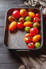 Colorful ripe tomatoes. Delicious vegetarian food. Dark background.