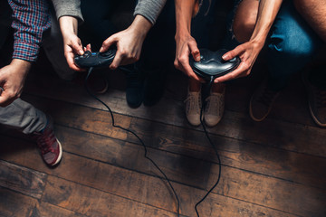 Unrecognizable people play video game, closeup view of hands with joysticks. Exciting competition, tension, pleasant entertainment, leisure activities concept