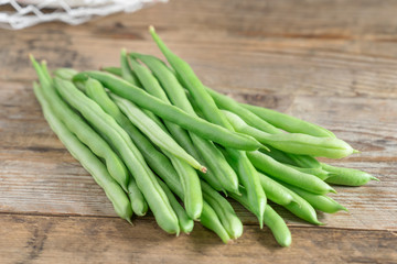 Green bean on wood background.