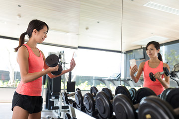 Woman practices lifting weights and tsking selfie in gym