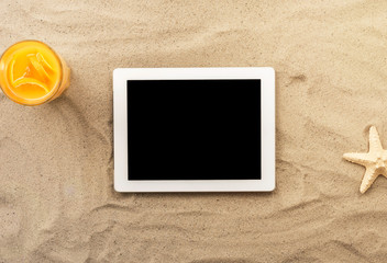 White digital tablet with copy space on the sand