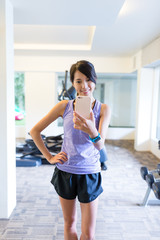 Sport woman taking selfie by mobile phone in gym