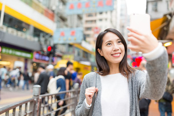 Woman taking selfie by cellphone in Hong Kong