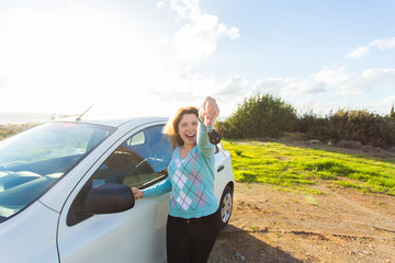 auto business, car sale, consumerism and people concept - happy woman holding new car key outdoor