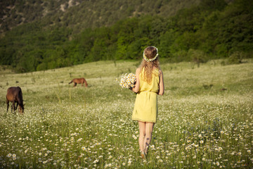 Beautiful lady with cute daughter on camomile field