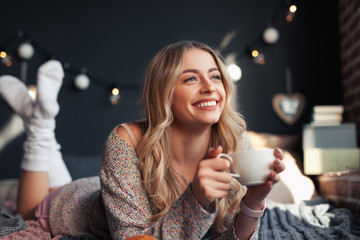 Happy woman having hot drink on bed