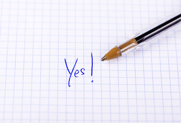 The word yes written on sheet of paper with pen.