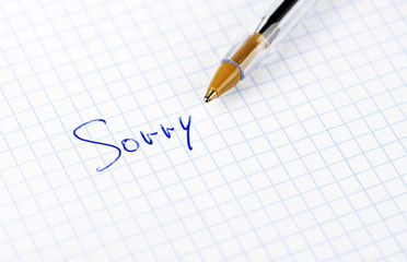 The word sorry written on sheet of paper with pen.