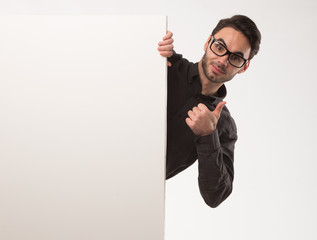 Young happy man showing presentation, pointing on placard over gray background