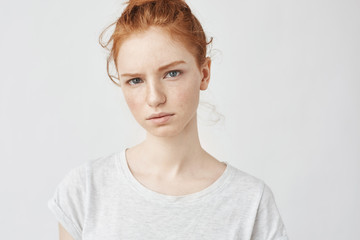 Portrait of young tender redhead teenage girl with healthy freckled skin wearing grey top looking at camera with serious expression. Caucasian woman model with ginger hair posing indoors