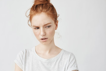 Portrait of beautiful dissatisfied redhead girl with freckles.