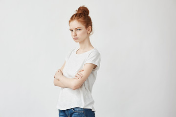 Portrait of redhead displeased girl with crossed arms. Copy space. Isolated on white .