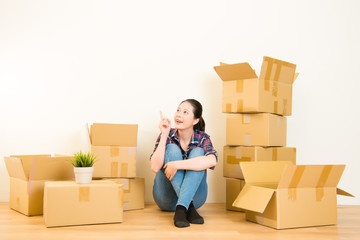 woman thinking unpacking boxes