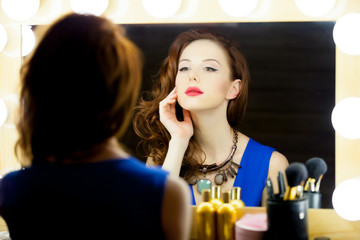 portrait of beautiful young woman  looking at herself in the mirror