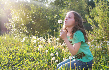 Teen blowing seeds from a dandelion flower in a spring park