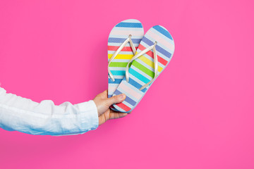 photo of male hand holding colorful sandals on the wonderful pink studio background