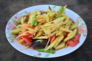 Green papaya salad Thai cuisine spicy delicious on wooden plate , SomTam