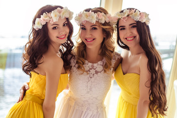 Beautiful Bride and two bridesmaids in yellow similar dresses together in a sea restaurant