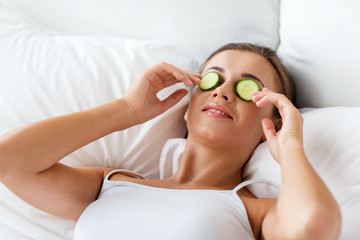 beautiful woman applying cucumbers to face at home