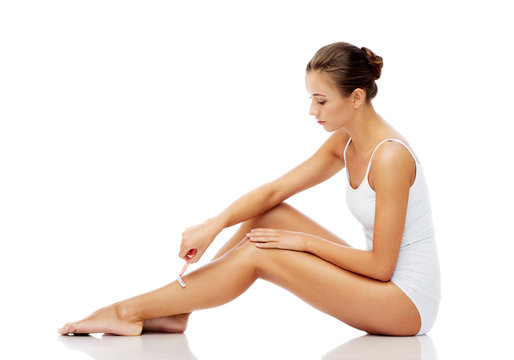 woman with safety razor shaving legs