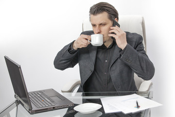 A young man is sitting in his office. He is drinking coffee and he is trying to make a phone call. He is also staring at the screen of his computer.