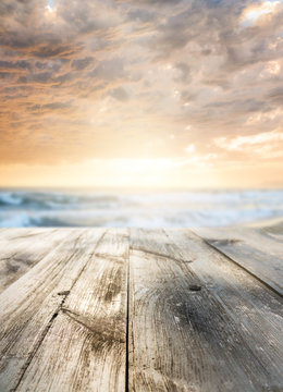 Wooden table and sunset at seaside. Focus on table, blurred background.