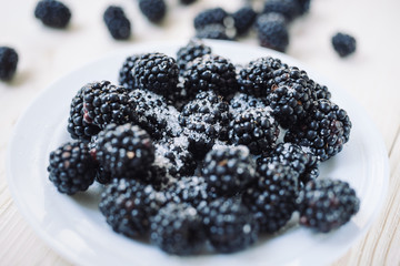 Ripe berries of dewberry on a white table on a wooden table. Healthy breakfast with vital vitamins. Ripe blackberry powdered with sugar.