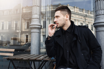 Attractive man in black clothes took sit to have cigarete.