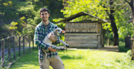 A young handsome and smiling farmer, holding a lamb young cub, has the experience to follow and care for live animals, on the background of nature and a barn, concept: ecology,livestock,bio,farming