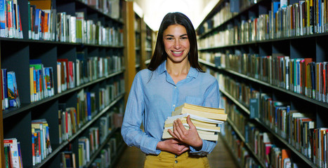 Portrait of a beautiful young woman smiling happy in a library holding books after doing a search and after studying. Concept: educational, portrait, library, and studious.