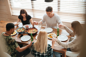 Group of people holding hands and praying at dinner table
