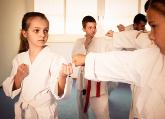 Happy children sparring in pairs in karate class