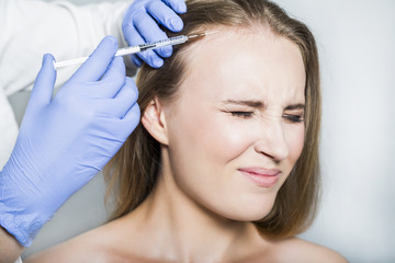 Doctor aesthetician makes head beauty injections to female patient