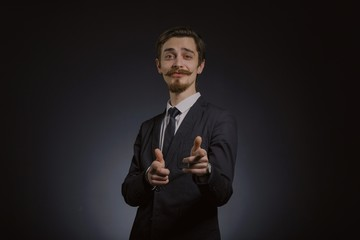 Studio portrait of a serious young businessman wearing a black suit on black background, copy space
