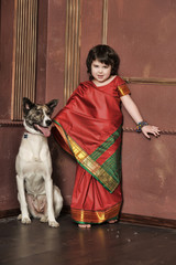 Little girl in red Indian sari and dog