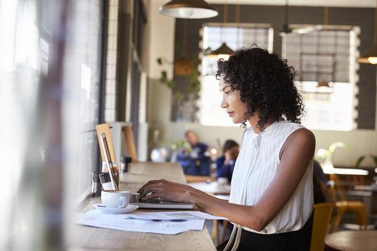 Businesswoman By Window Working On Laptop In Coffee Shop